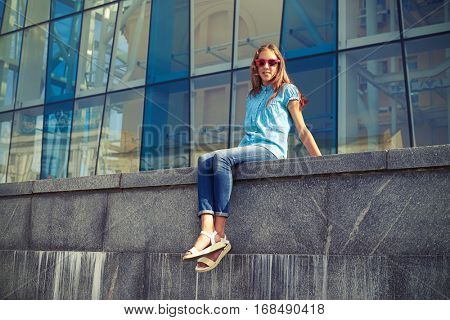 The shrewd look of young girl wearing sunglasses; sitting against business center