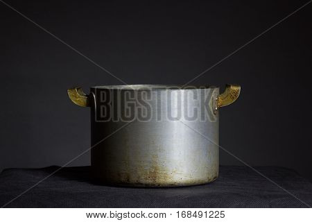 Belarus Minsk - Old metal pot with handles on a black background placed on a table covered with a black cloth pot is made in the USSR scorched in the fire pan.