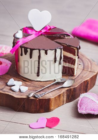 Three layered Valentine's Day cake with heart shaped decoration and wrapped with pink ribbon standing on a wood cut stand