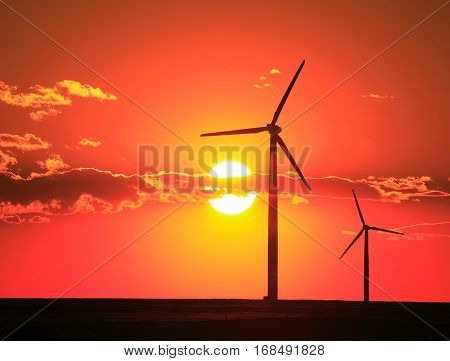 A tall wind turbine and a bright orange sunset