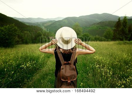 Woman Traveler With Backpack Holding Hat And Looking At Amazing Mountains And Forest, Wanderlust Tra