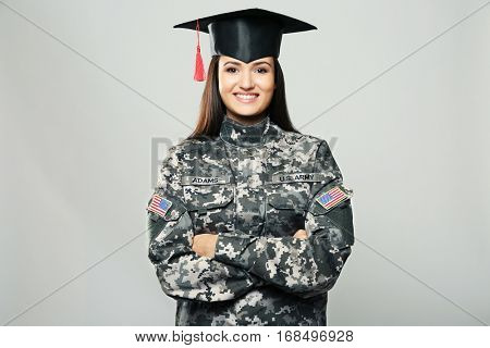 Pretty female soldier wearing graduation cap, on grey background