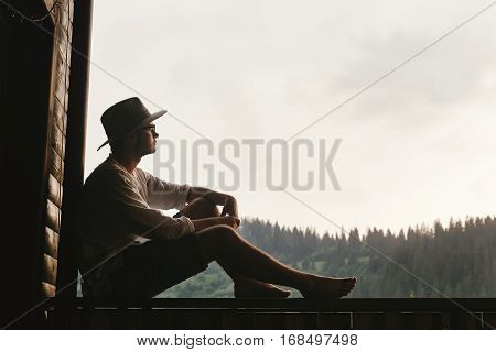 hipster man sitting on porch of wooden house looking at mountains in evening calm moment summer vacation concept space for text
