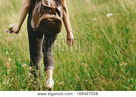 Stylish Hipster Woman Walking In Grass And Holding  In Hand Herb  Wildflowers  In Summer Mountains,