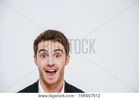 Close up portrait of a happy cheerful man peeking out from the edge isolated on a white background