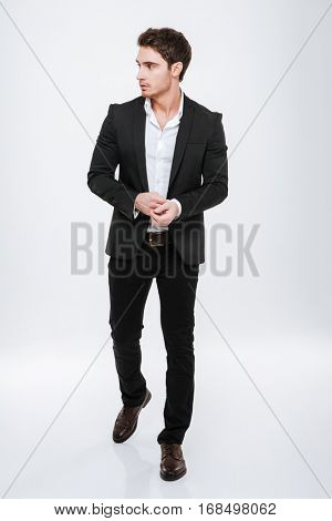Full-length portrait of a handsome businessman standing and posing isolated on a white background