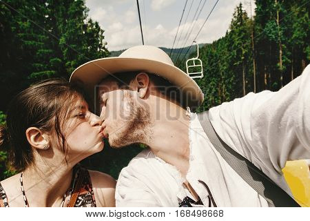 stylish hipster couple kissing on chairlift in summer mountains travel together concept