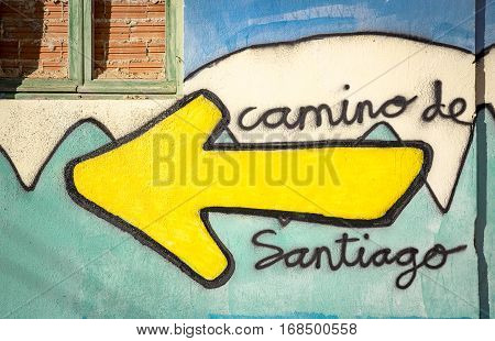 Camino de Santiago words and a yellow arrow painted on a wall on the way to Santiago