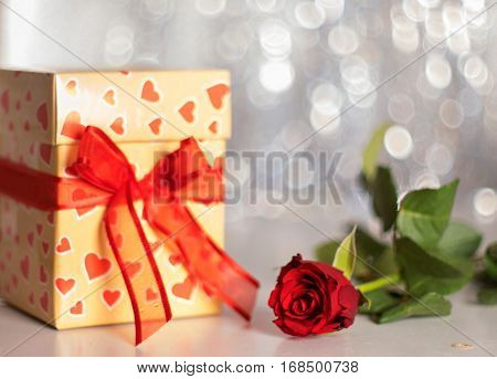 Cute small gift and rose composition. Horizontal studio shot.