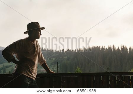 Hipster Man Standing On Porch Of Wooden House And Relaxing Looking At Mountains In Evening, Calm Mom