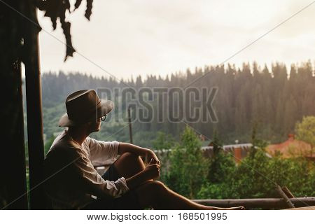 Hipster Man Sitting On Porch Of Wooden House  Looking At Woods In Evening, Calm Moment, Summer Vacat