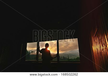 Silhouette Of Woman In Sunshine In Wooden Cottage Window  With View On Sunset In Mountains, Tranquil