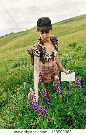 Stylish Hipster Woman Traveler Holding In Hand Map And Wildflowers And Gathering Lupin In Mountains,