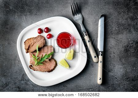 Tasty grilled steak slices with cranberry sauce, lime and arugula on plate