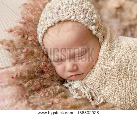 cute sleeping newborn baby in hat on fluffy blanket, closeup