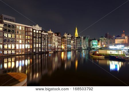 Amsterdam canal with typical houses and Oude Kerk church during twilight blue hour, Holland, Netherlands