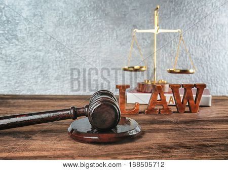 Court gavel and word LAW made of letters on wooden table