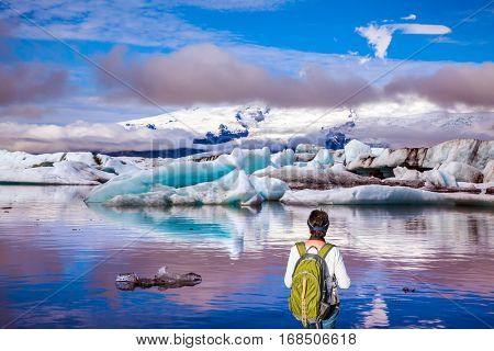 The woman - tourist with a green backpack watching the moving ice. Sunrise in the Ice Lagoon. Ice floes are reflected in the smooth water surface. The concept of extreme northern tourism