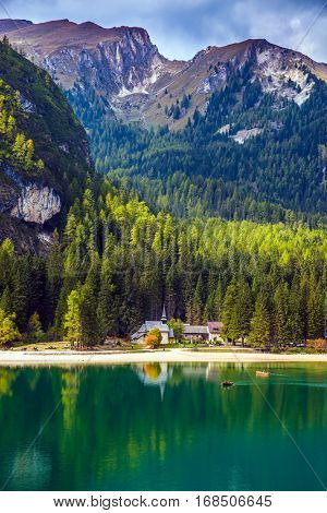 Green water reflects the surrounding mountains and forest. South Tyrol, Italy. Magnificent lake Lago di Braies. The concept of walking and eco-tourism