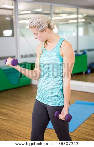 Fit woman lifting dumbbells in fitness studio