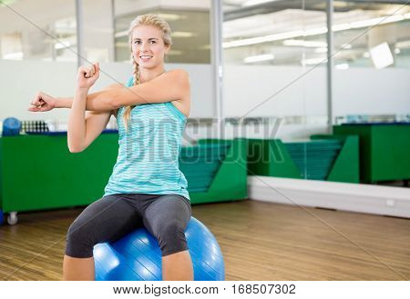 Fit woman stretching and sitting on exercise ball in fitness studio