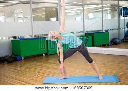 Fit woman doing yoga on mat in fitness studio