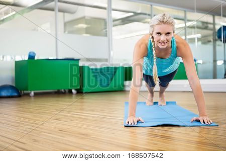 Fit blonde planking on mat in fitness studio