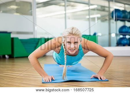 Fit blonde doing push up on mat in fitness studio