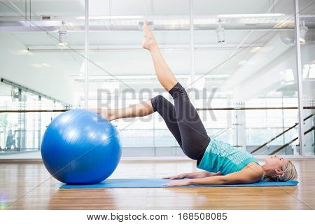 Fit blonde on mat exercising with fitness ball in the studio