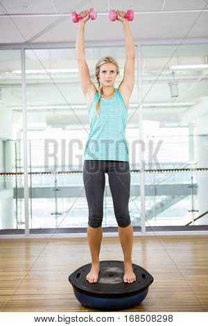 Fit blonde standing on bosu ball and lifting dumbbells in fitness studio