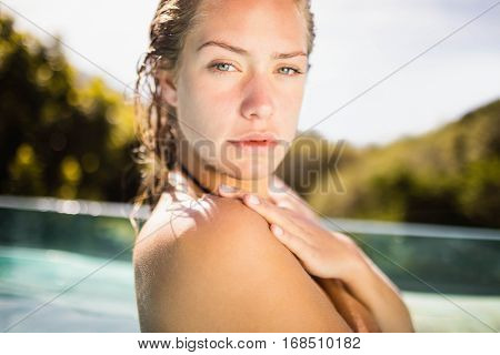 Unsmiling blonde in the pool crossing arms and looking at the camera