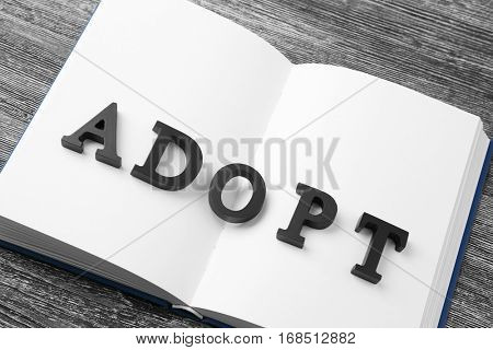 Word ADOPT and open notepad on wooden background