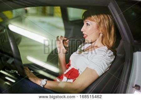 Young woman with sunglasses in hand sits on driver seat in modern car at underground parking.