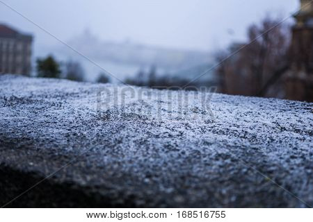 A shallow focus highlights frost on top of a stone wall