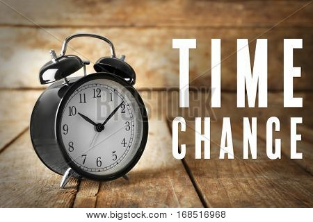 Alarm clock and text TIME CHANGE on wooden background