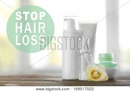 Text STOP HAIR LOSS on background. Set of cosmetic products on wooden table