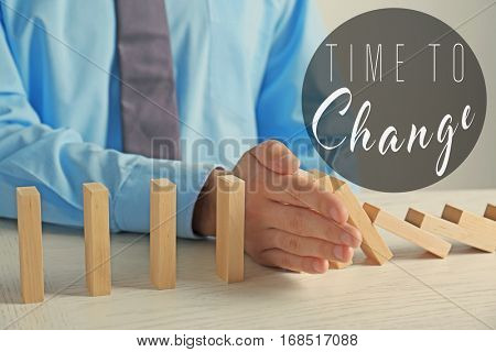 Male hand stopping falling dominoes and text TIME TO CHANGE on background