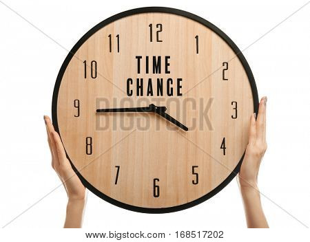 Female hands holding clock with text TIME CHANGE on white background