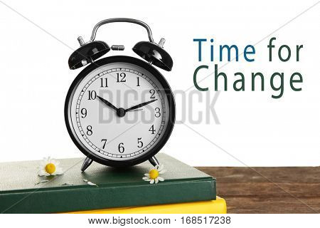 Alarm clock and books on table. Text TIME FOR CHANGE on white background