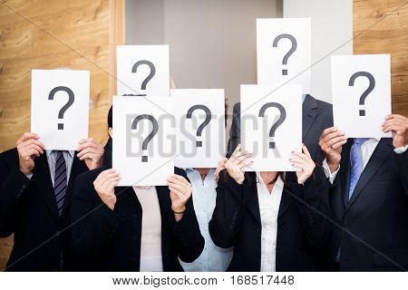business team holding pieces of paper with question marks. concept shot used to depict cluelessness or confusion.