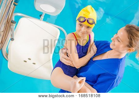 Children Rehabilitation Session in the Swimming Pool. Children Hospital Theme. Medical Practitioner with Young Disabled Girl on Hands