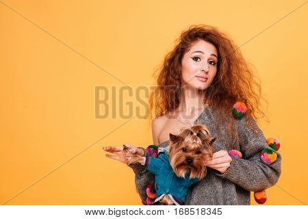 Portrait of beautiful young red head girl holding cute yorkie isolated on orange background
