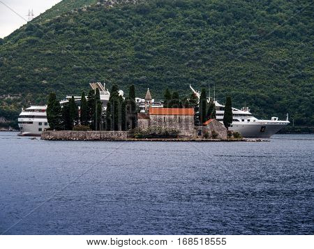 a cruise ship behind a small church. nearby kotor, montenegro
