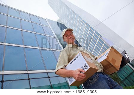 a smiling delivery person is standing in front of modern buildings, holding some packets.