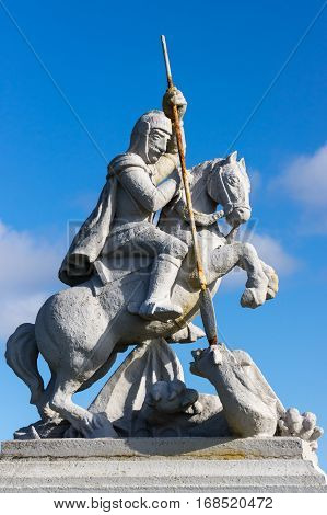 Orkneys Scotland - June 5 2012: Closeup of white concrete statue of Saint George sitting on horse defeating a dragon against deep blue sky. Outside the Italian Chapel on Lamb Holm Island. Rusty spear.