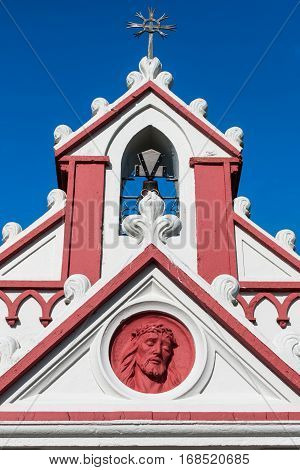 Orkneys Scotland - June 5 2012: Closeup of top of the white and maroon painted facade of the Italian Chapel on Lamb Holm Island against deep blue sky. Red Jesus face cross and bell.