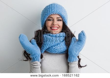 Beautiful woman in warm hat, mittens and scarf on white background