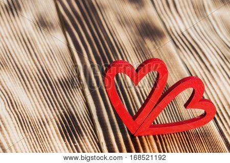 Two red painted hearts on wooden background