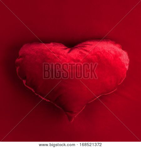 Red pillow heart on red fabric background, Valentines day