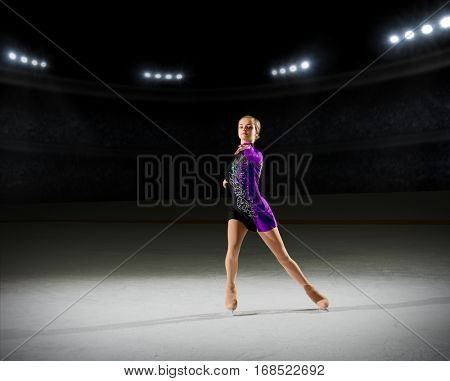 Young girl figure skater (on ice arena with spotlights version)